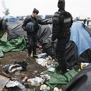 Prestwich and Whitefield Guide: Police officers take positions in a makeshift camp housing hundreds of illegal migrants from Syria, Afghanistan and Africa, after French authorities started to clear out camps in Calais