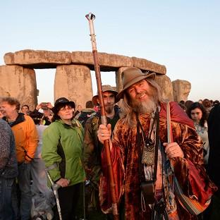 Crowds gather at dawn amongst the stones at Stonehenge in Wiltshire for
