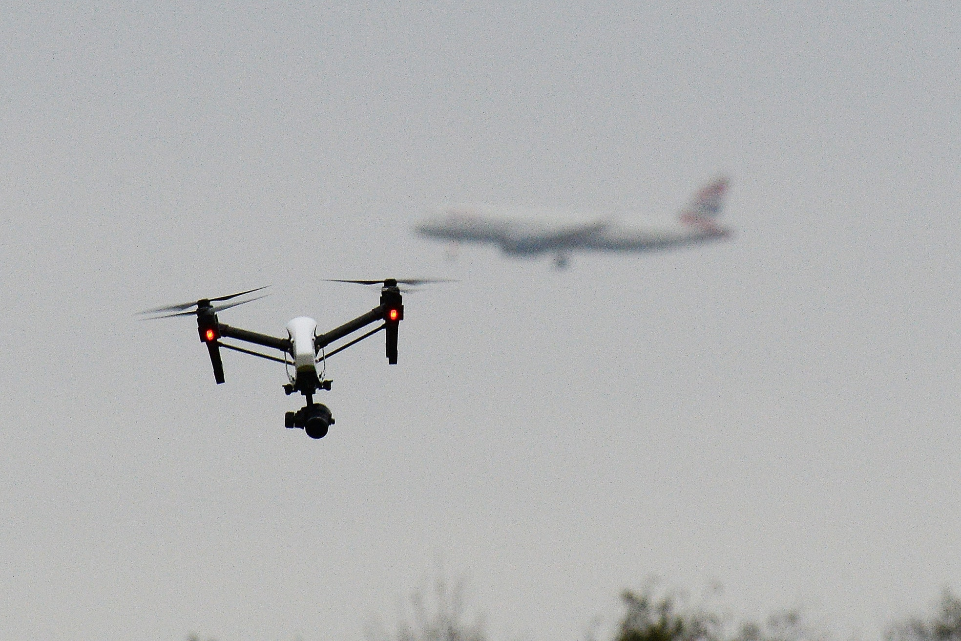 A drone flies in west London as a British Airways plane prepares to land at London Heathrow airport (John Stillwell/PA)